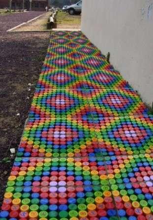 Совет! Из крышек использованных пластиковых бутылок можно сделать дорожки на даче.